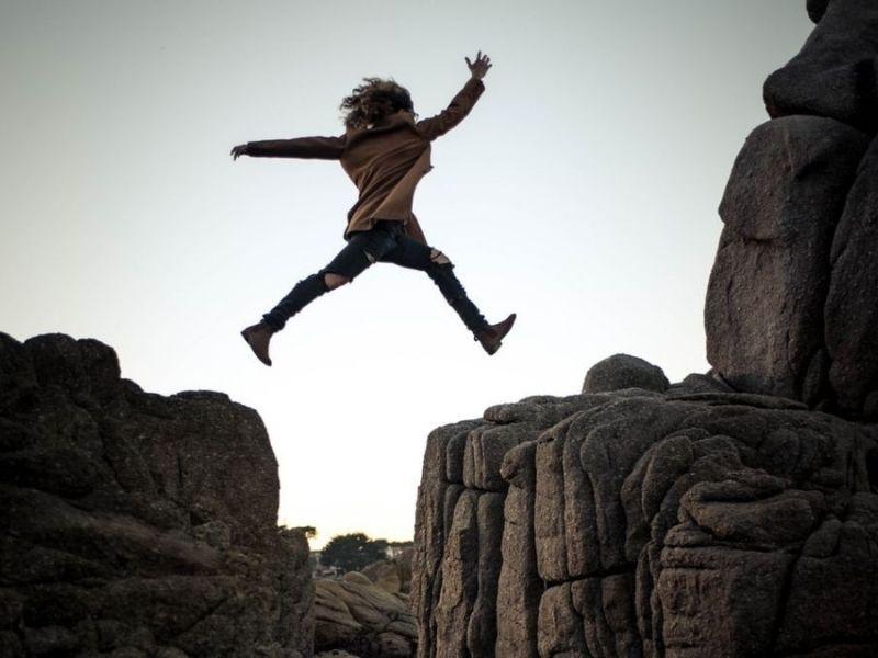 Frau-springt-über-Klippe